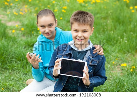 brother and sister with tablet PC and phone - stock photo