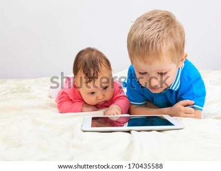 brother and sister with touch pad at home, modern communication - stock photo
