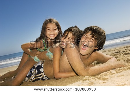 Brother and sisters having fun at beach on a sunny day - stock photo