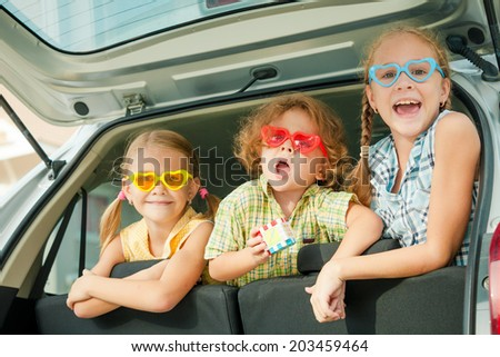 Brother and sisters  sitting in the car at the day time - stock photo