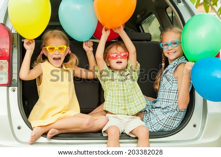 Brother and sisters with balloons sitting in the car at the day time - stock photo