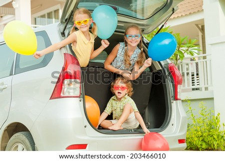 Brother and sisters with balloons sitting in the car near house at the day time - stock photo