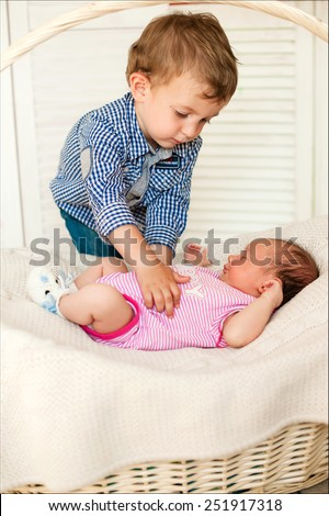 brother gently touched the sleeping little sister - stock photo