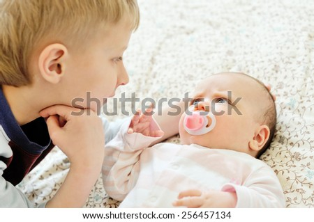 brother glad to see his baby sister - stock photo