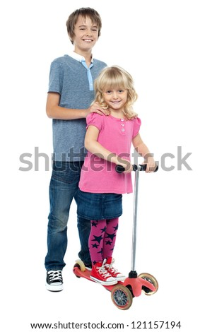 Brother holding her sister as she rides her toy scooter. Casual studio shot. - stock photo