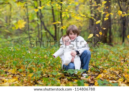 Brother holding his baby sister both in white jackets in an autumn park with yellow trees - stock photo