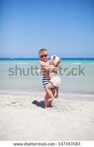 brother holds sister near the sea