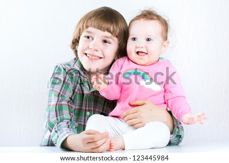 Brother hugging his baby sister, both wearing green and pink shirts - stock photo