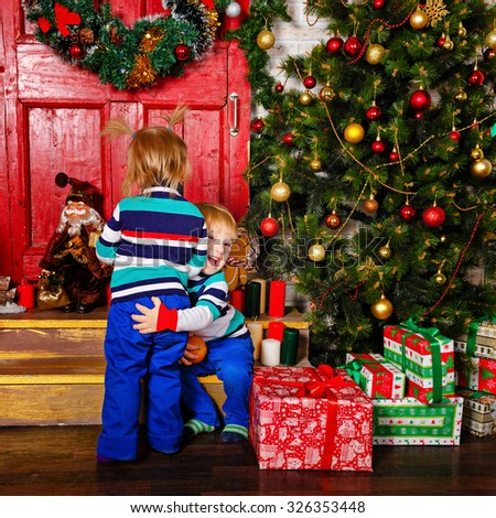 Brother hugging his sister near a Christmas tree. Cute little kids. Happy family and Merry Christmas. - stock photo