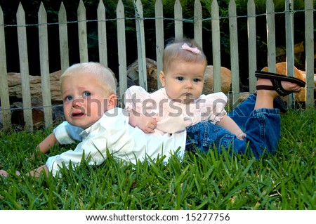 Brother is not happy about his sister's affection.  Baby girl lays across small boys back.  Both are laying on the grass. - stock photo