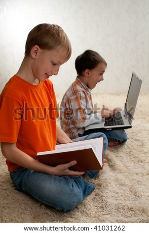 brother is reading a book and a younger brother with a laptop