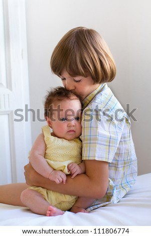 Brother kissing his baby sister - stock photo