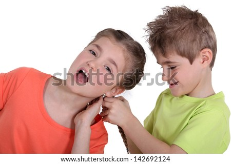 Brother pulling sister's hair - stock photo