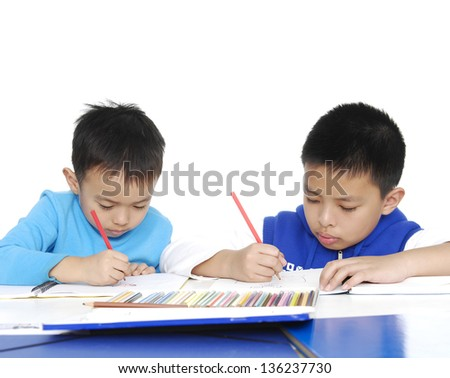Brother School boy sitting and writing in notebook on white background - stock photo