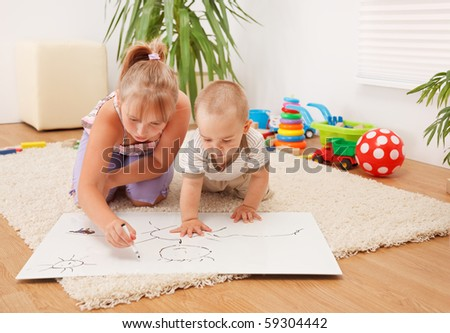 Brother watching his sister drawing on white sheet in the room - stock photo