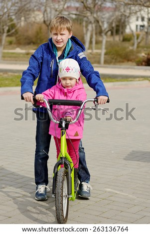 brother wheeling her sister on the scooter - stock photo