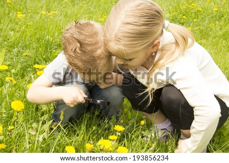 brother with her sister treated flower through a magnifying glass