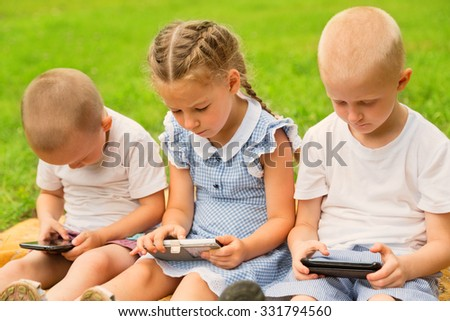 Brothers and sister using smartphones sitting on the lawn in park. Used retro filter. - stock photo