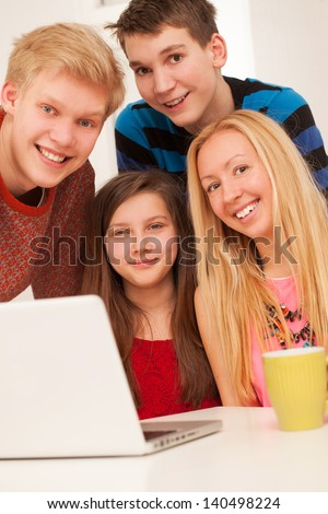 Brothers and sisters having fun at home with notebook - stock photo