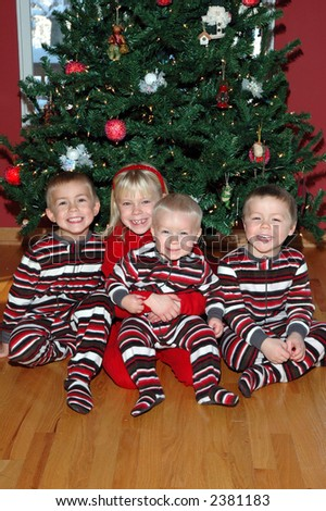 brothers and sisters in front of christmas tree - stock photo
