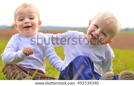 Brothers can be happy friends. Sitting in the nature. Child concept.
