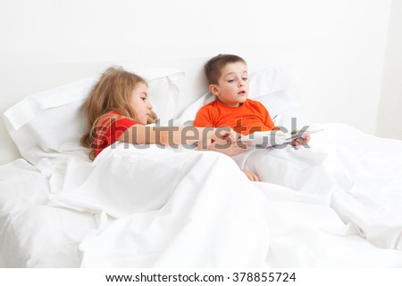 brothers girl and boy reading a book in bed before sleep
