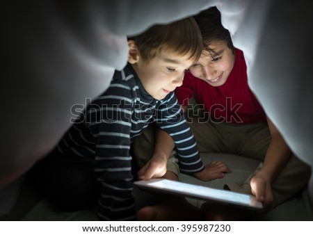 Brothers kids with tablet computer under blanket at night in a dark room