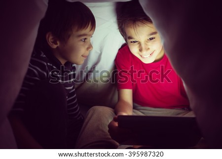Brothers kids with tablet computer under blanket at night in a dark room - stock photo