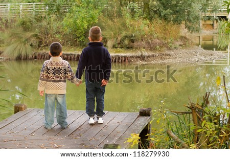Brothers looking out across a pond in Autumn