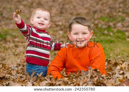 Brothers playing in leaves outdoors during autumn - stock photo