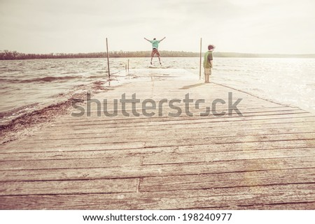 Brothers Playing on a dock