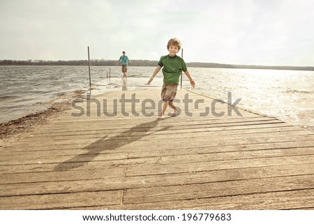 Brothers playing on a dock in the summertime