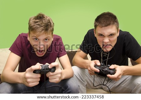 Brothers playing video games funny selective focus on younger brother - stock photo