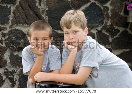 Brothers pose on a bar stool to show their boredom during a photo shoot. - stock photo