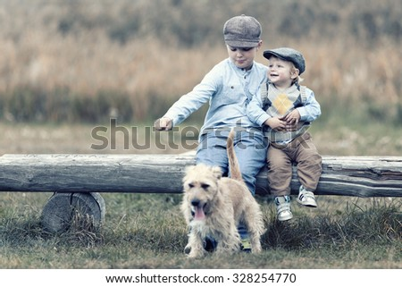 Brothers sit on a bench with dog in nature on autumn day, Retro look - stock photo