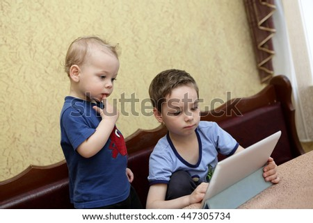 Brothers using tablet PC in a cafe - stock photo
