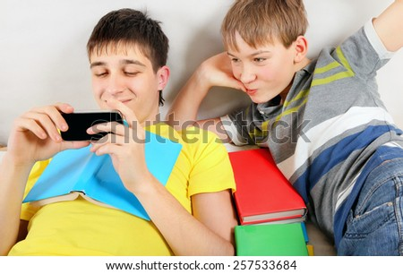 Brothers with a Books and Cellphone on the Bed - stock photo