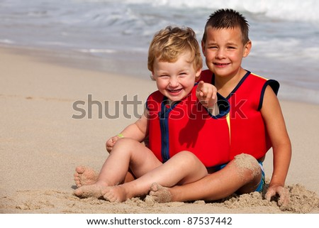 brothers with life jackets on a beach - stock photo