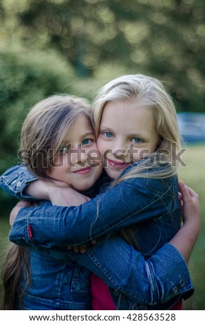 Brown and blond haired cute little girls friends smiling and hug. - stock photo