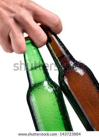 Brown and green beer bottles in a hand, close up - stock photo