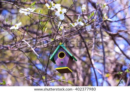 Brown and green birdhouse hanging in on tree branch with spring flowers, foliage and blue sky blurred in background - stock photo