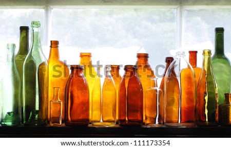 Brown and green old glass bottles on windowsill, with curtain. Closeup, daylight. - stock photo