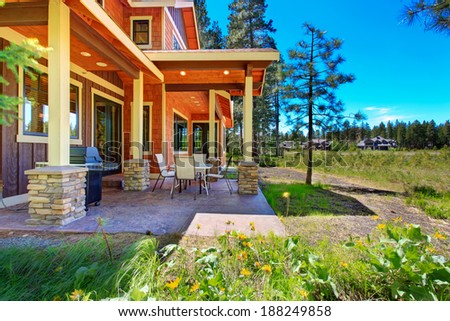 Brown and orange siding house with column backyard porch. Patio area view - stock photo