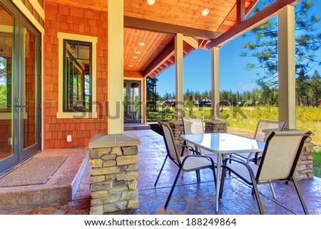 Brown and orange siding house with column backyard porch. Patio area view