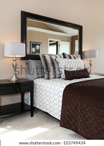 Brown and white bedroom close up with mirror and carpet. - stock photo