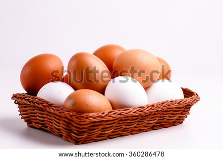 Brown and white chicken eggs lying in a wicker basket.
