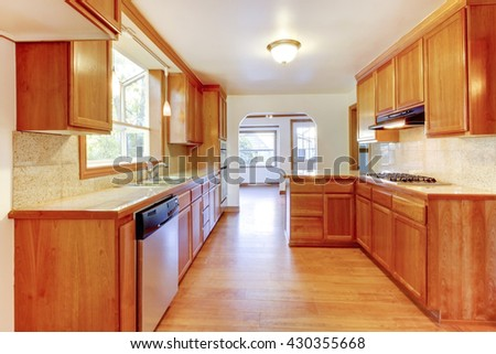 Brown and white  kitchen interior with hardwood floor and white ceiling - stock photo