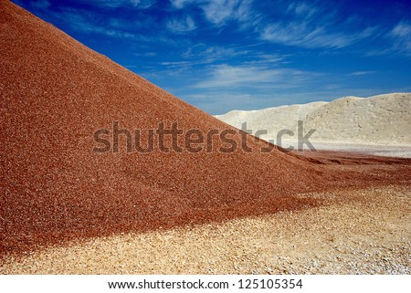 brown and white sandheaps under blue sky in mine at high noon - stock photo