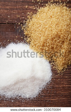 Brown and white sugar on brown wooden background