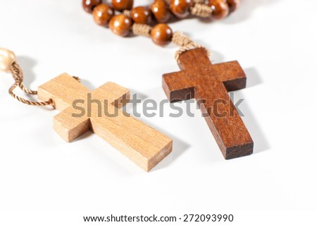 Brown and yellow christian cross necklace on white background.